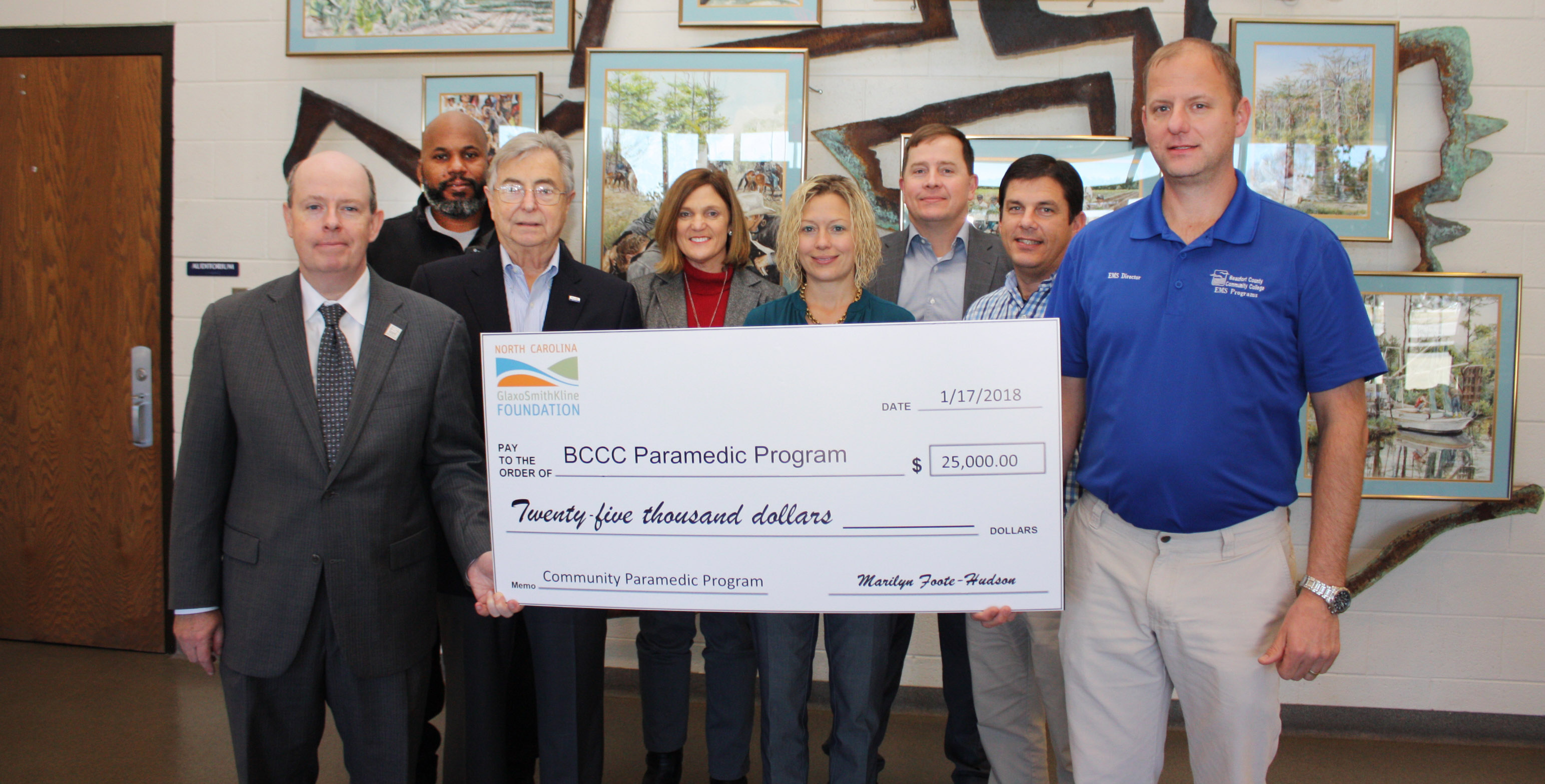 Seven people hold a large check.