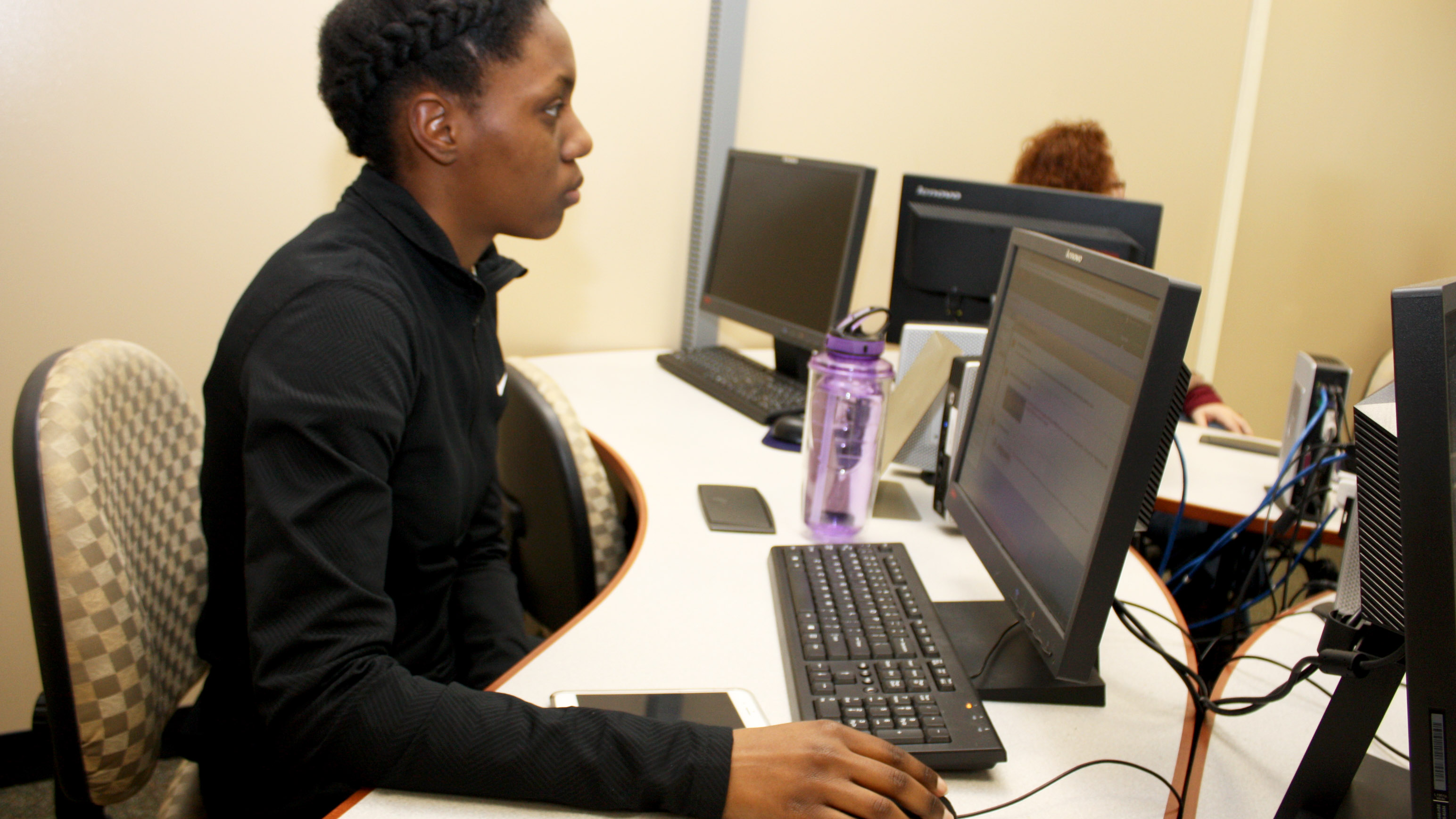 A female student in front of a computer.
