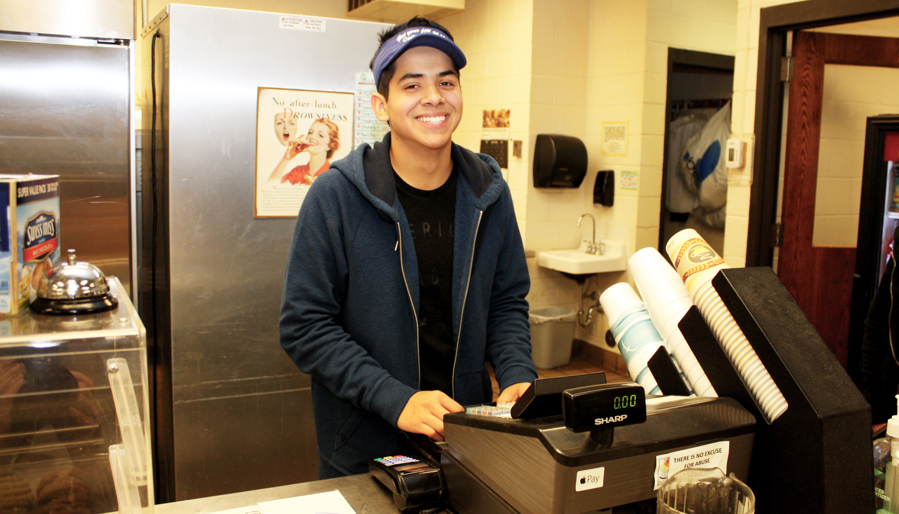 Andres Rodriguez behind the register at the Campus Grill. The diligent student will finish his program a year early, with an extra degree, and manages a part-time job.