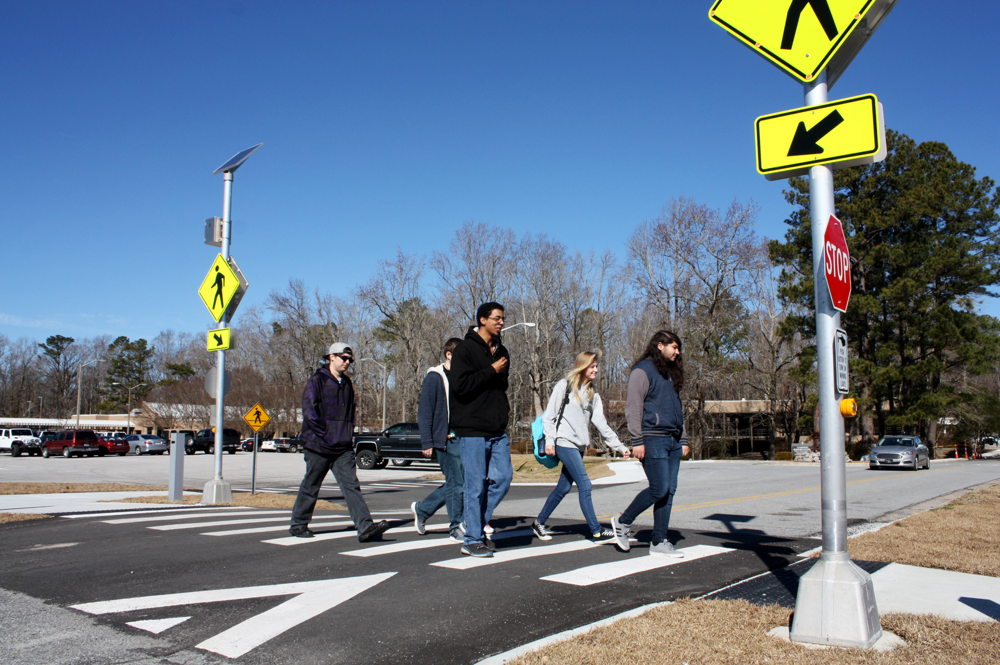 Five students cross at a protected intersection.