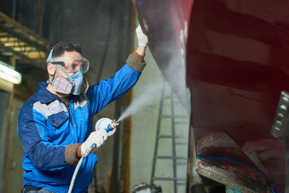 a person with PPE spraying a boat