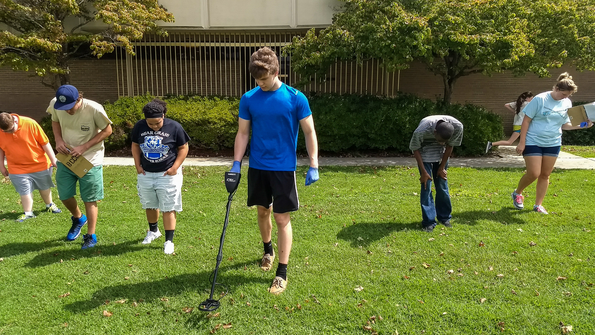 A student uses a metal detector while other students look at the grass.