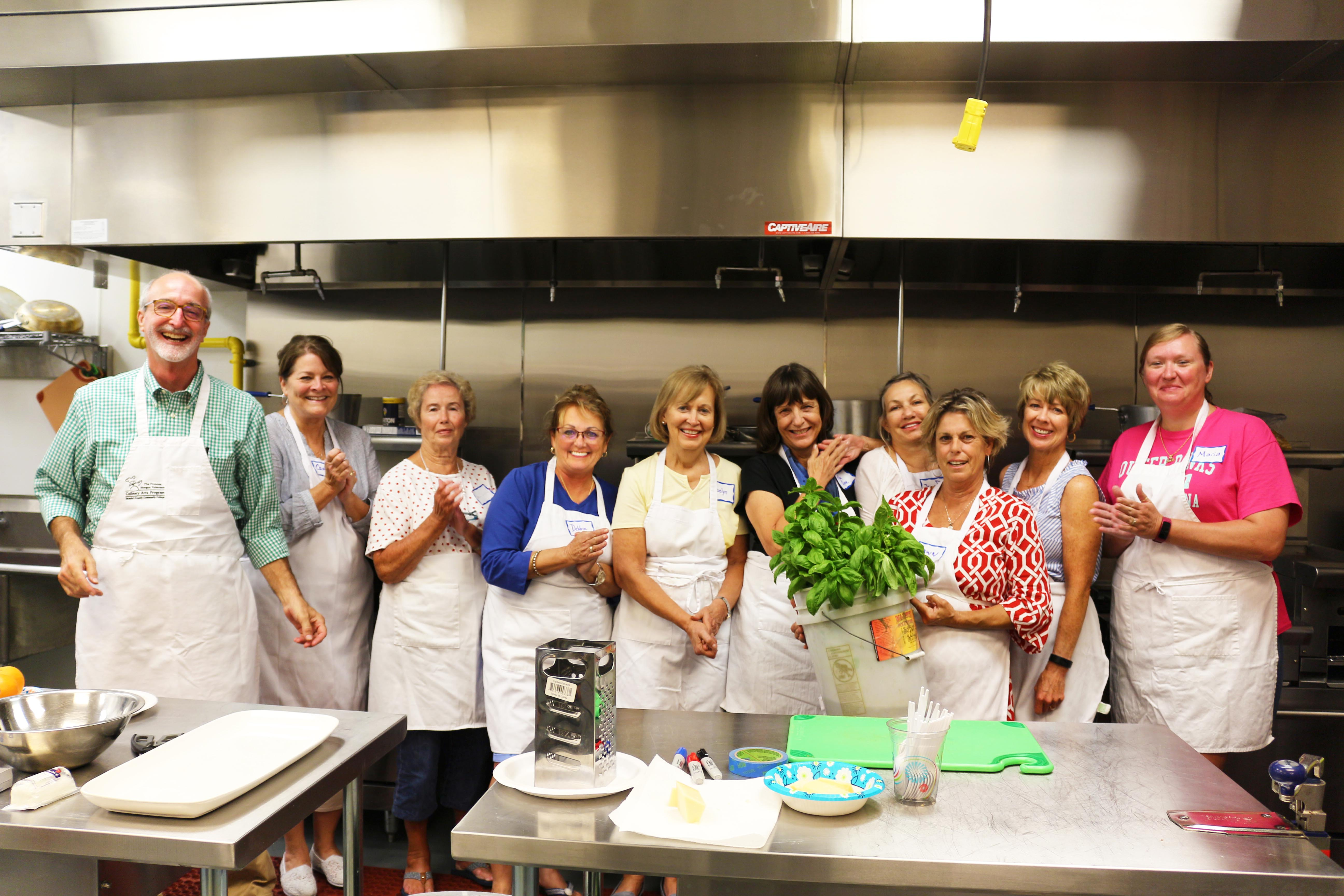 A cooking class lined up holding a bucket of basil.