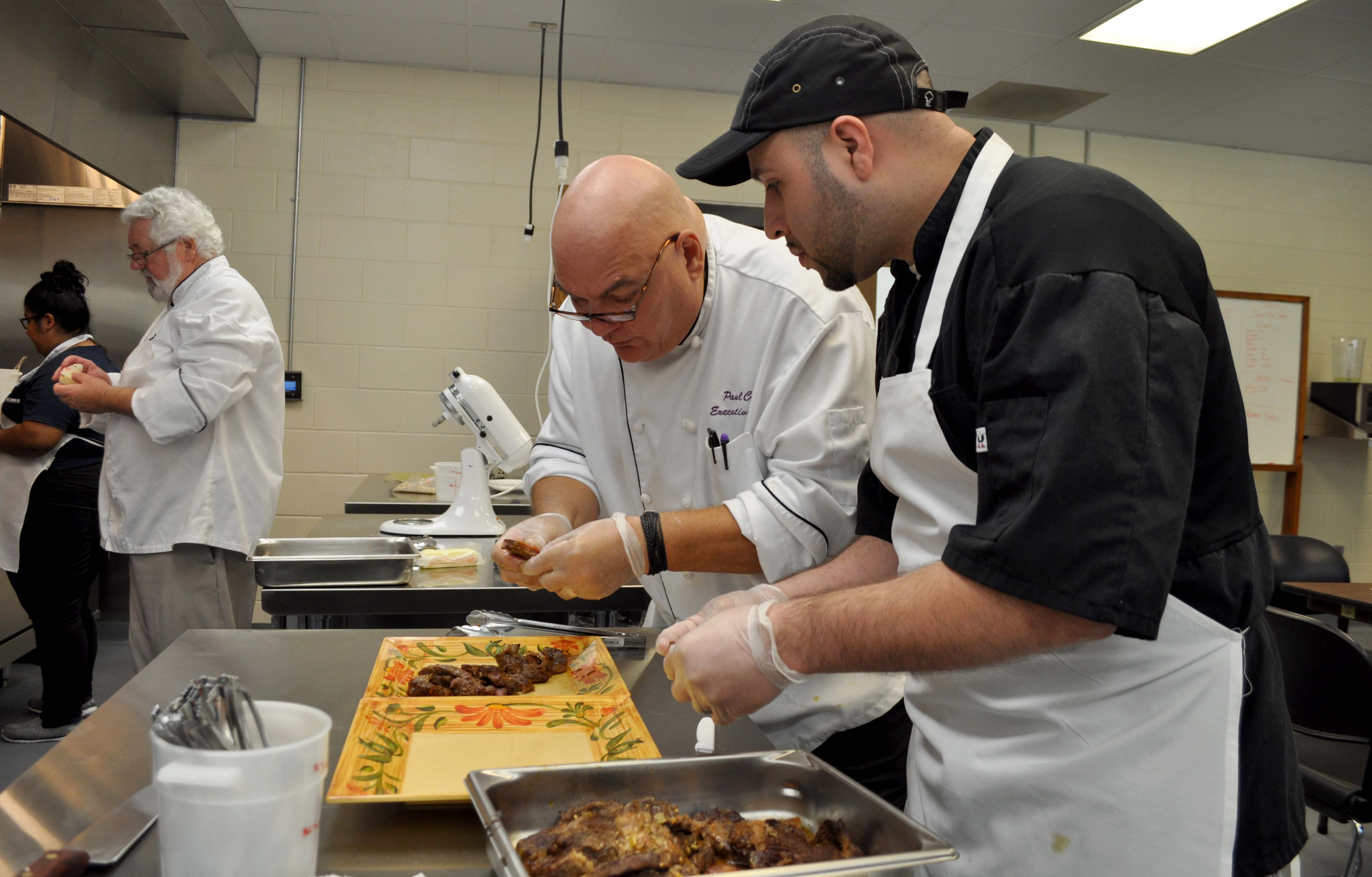 Cooking instructor shows student how to plate food.