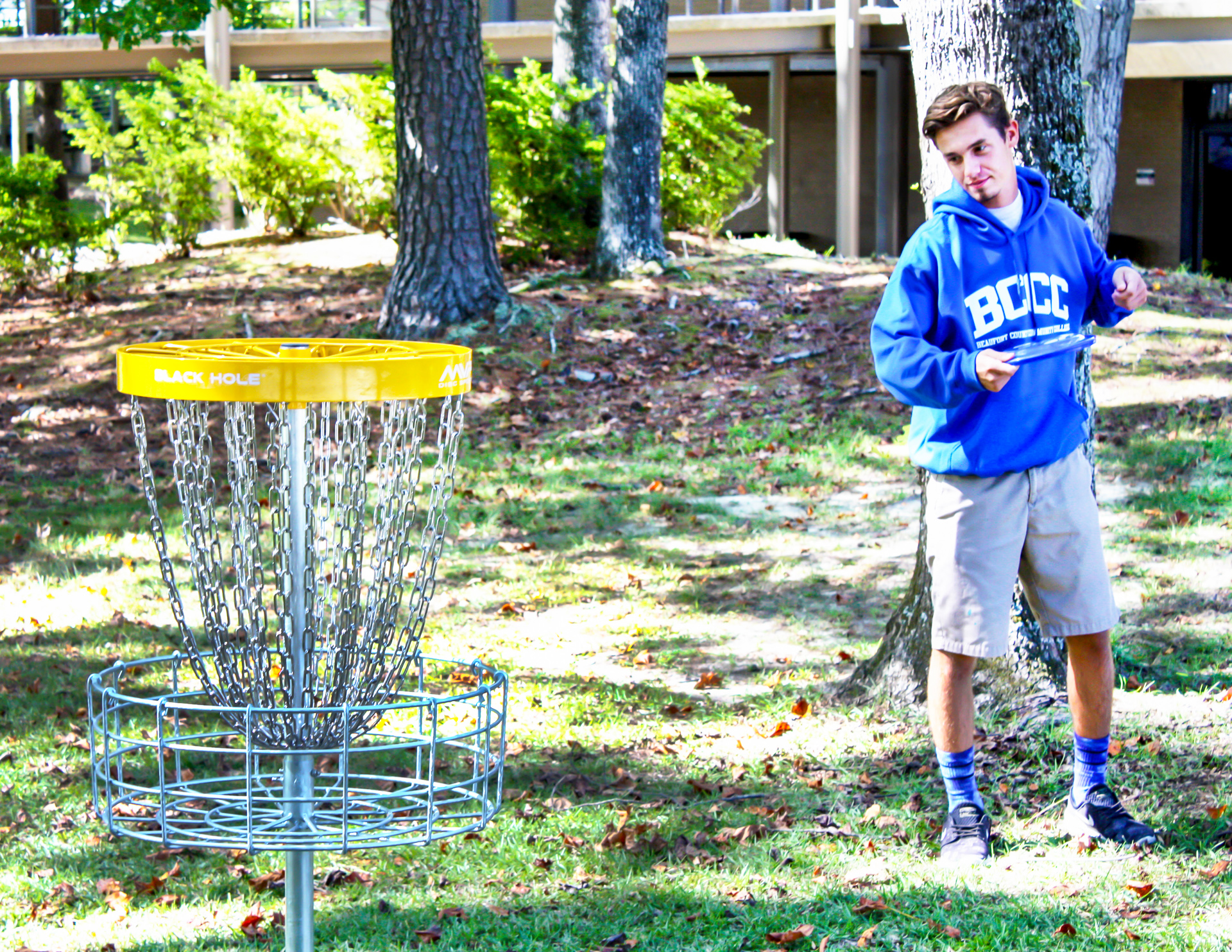 A student in a BCCC hoodie with a disc golf basket.
