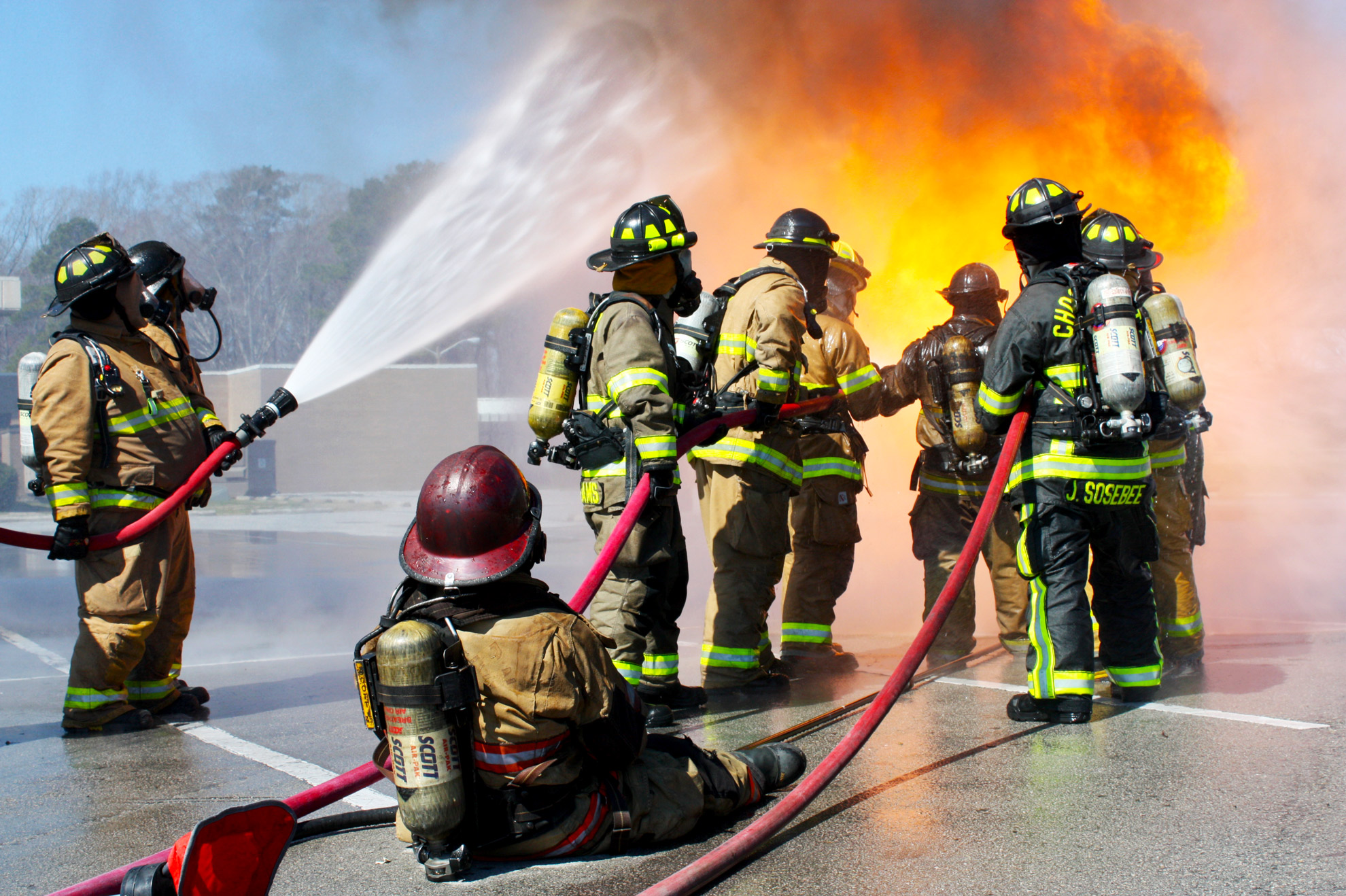 A team of firefighters practices putting out a live fire.