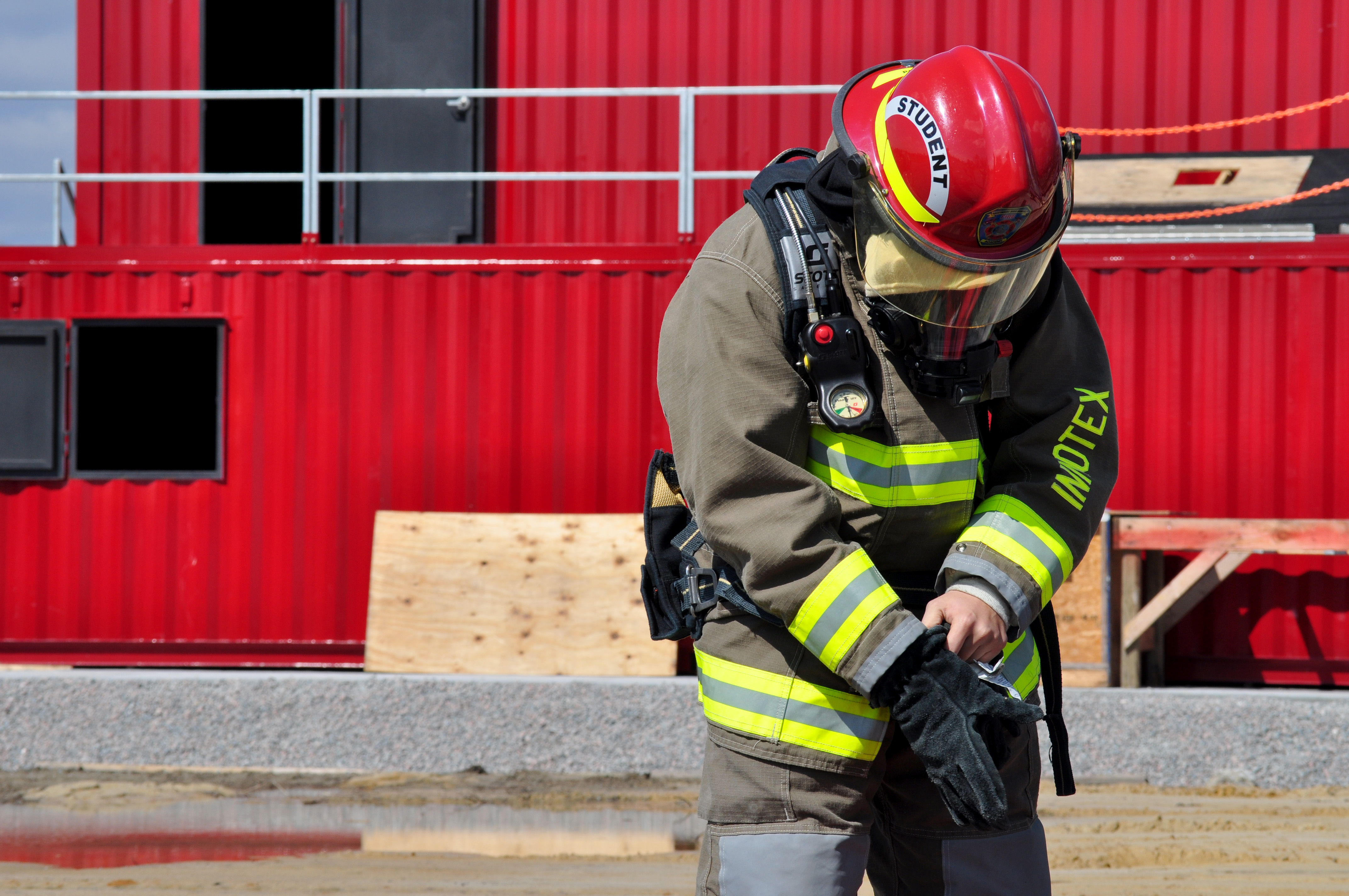 A student firefighter stands in front of a red training area.