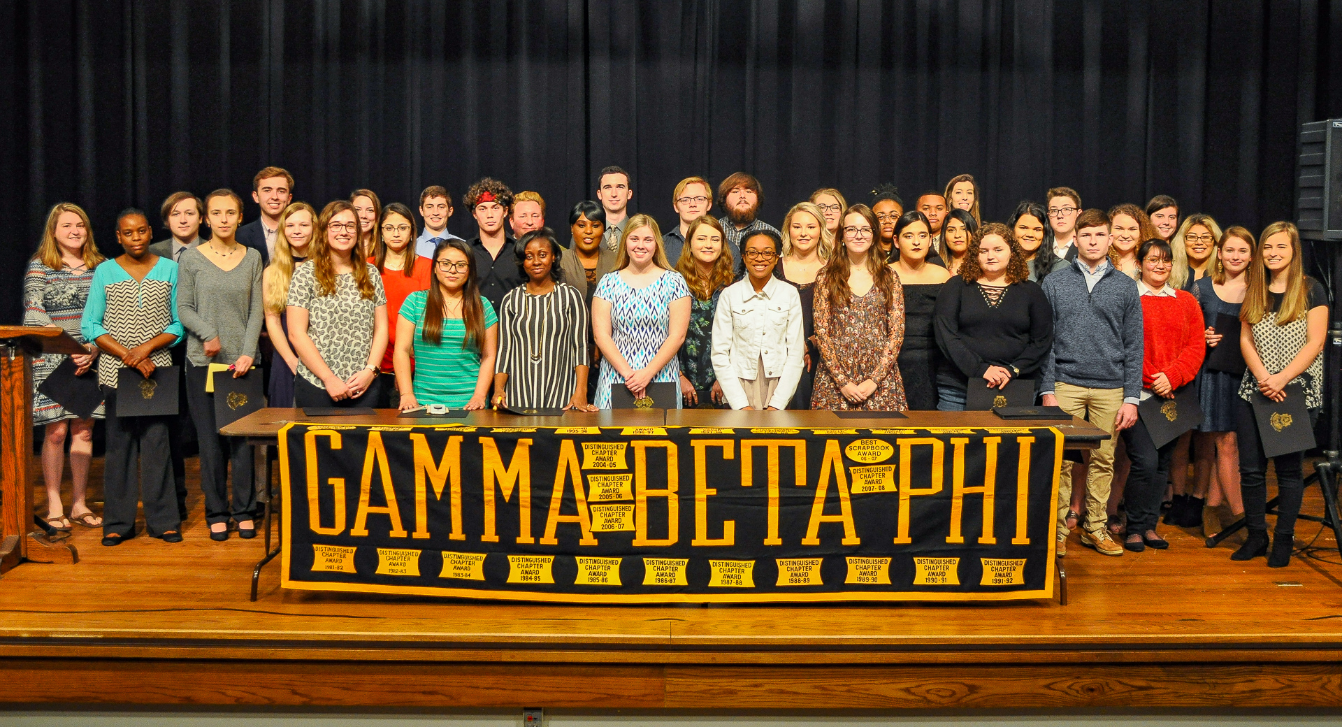 A large group behind a banner reading Gamma Beta Phi.