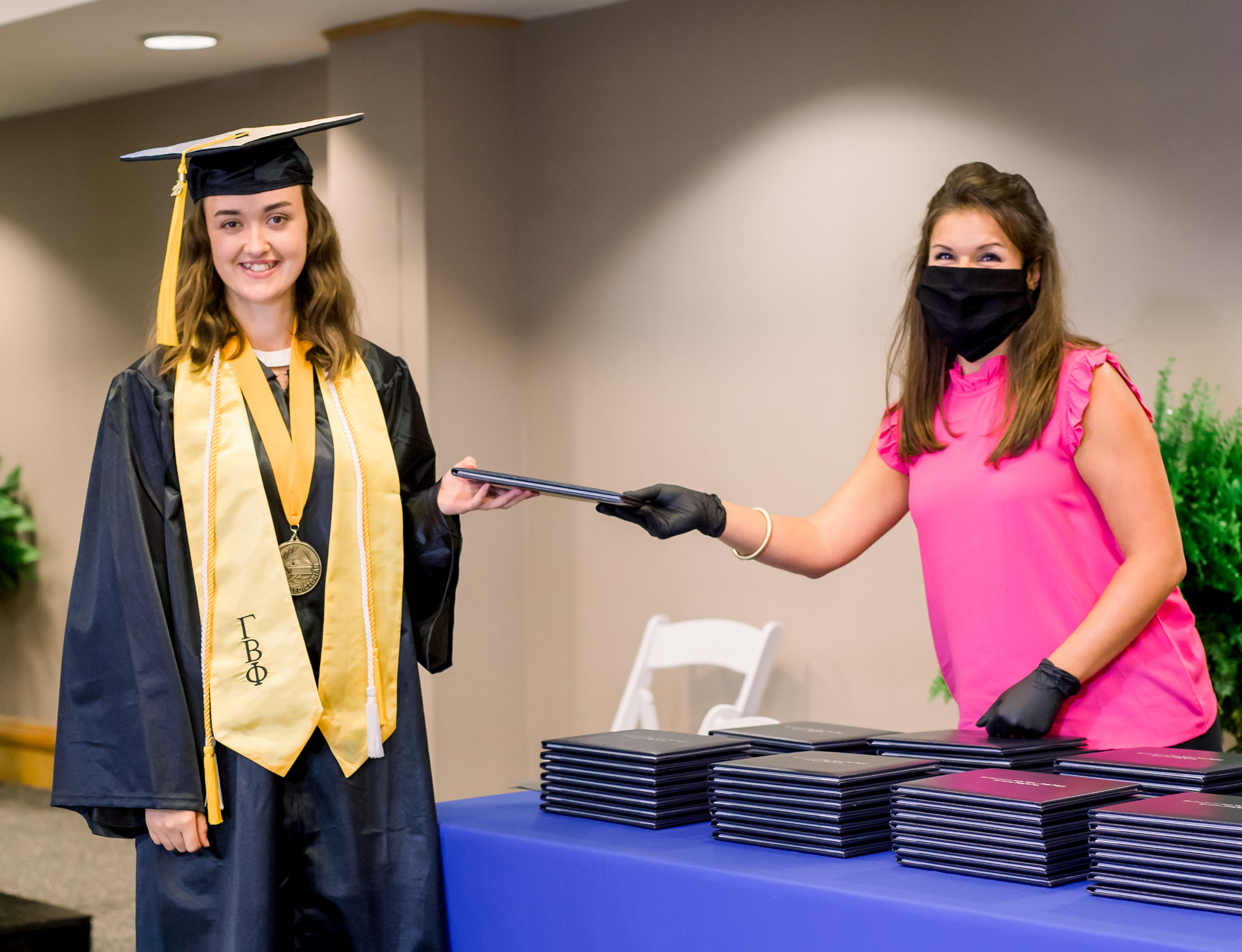 A person in graduation gear accepts a diploma