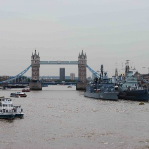Photo of metropolitan city in London a ocean view of large bridge, various boats , cruise ships, cargo ship, tourist boats